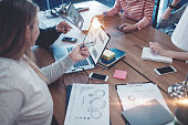 Young business team working together. Group meeting in the office. Paperwork and laptop on the table. Woman pointing to the screen. Four people. Intentional lens flares