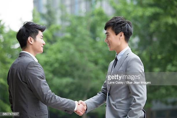 Young business person shaking hands outdoors