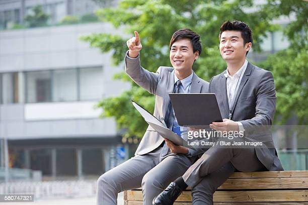 Young business person working with laptop outdoors