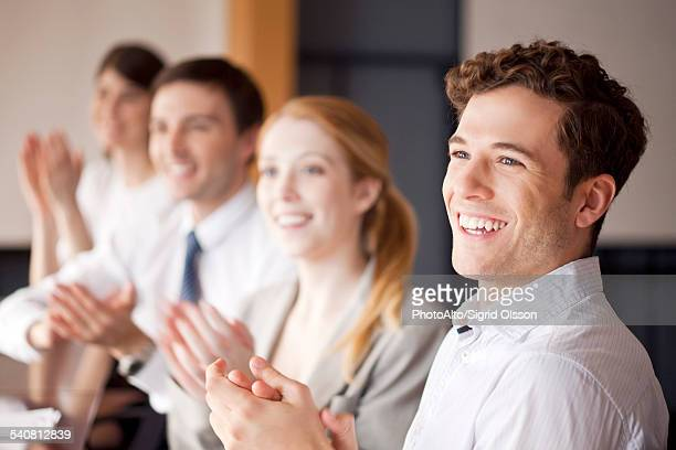 Young business professionals applauding during meeting