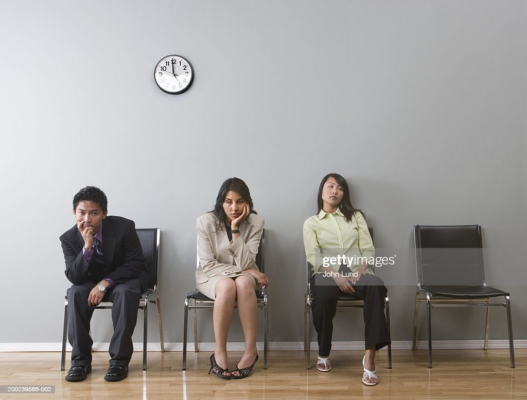 Young business professionals, sitting in waiting room, looking bored : Stock Photo