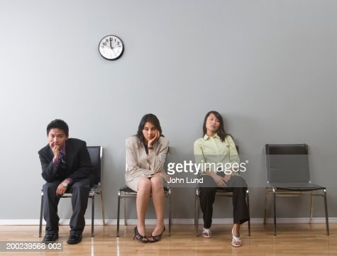 Young business professionals, sitting in waiting room, looking bored : Foto de stock