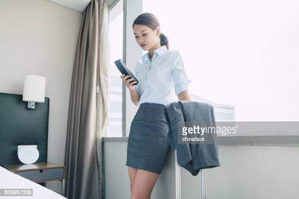 young business woman dialing on telephone in room