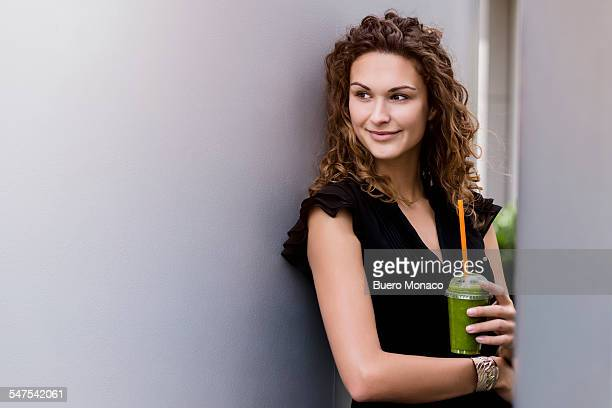 young business woman drinking smoothie outside