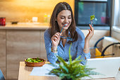 Young business woman eating salad at home, having healthy lunch at workplace. Portrait of pretty young woman eating salad and working at home.