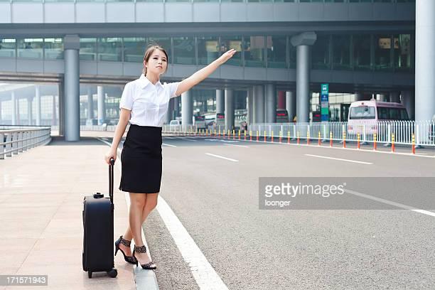 Jeune femme d'affaires de héler un taxi à l'aéroport