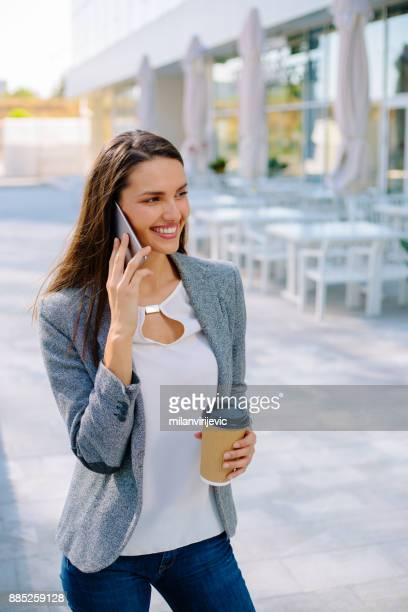 Young business woman having phone call outdoors