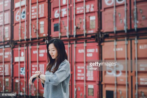 Young business woman holding smartphone on hand and checking time in container terminal