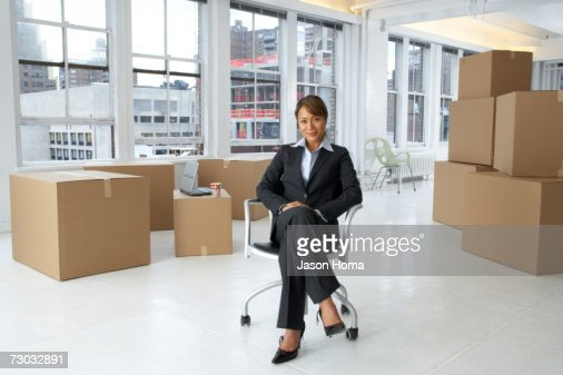 Young business woman in empty office surrounded by boxes : Stock Photo