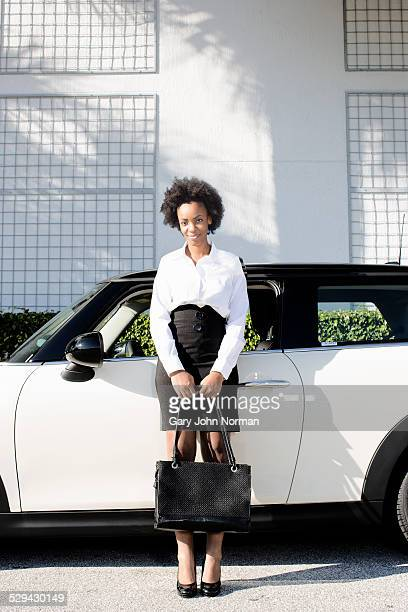 Young business woman leaning on her car.