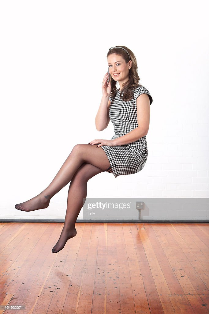 Young business woman making a phone call floating mid air