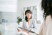 Cheerful business lady having meeting with coworker