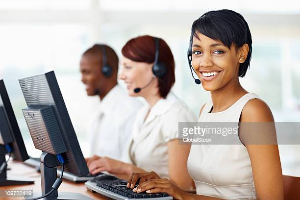 Young business woman poses for photo in call center