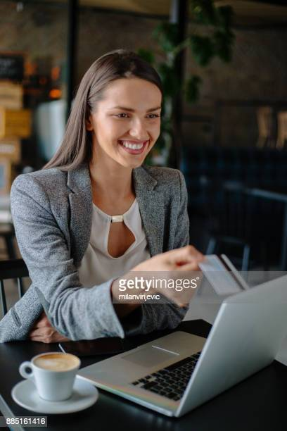 Young business woman purchasing online in cafe bar