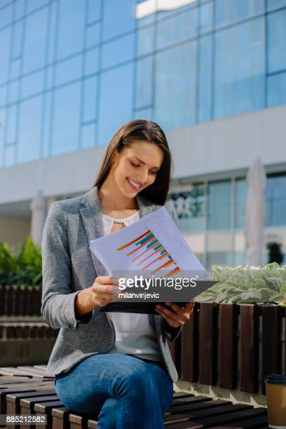 Young business woman reading sales reports outdoors