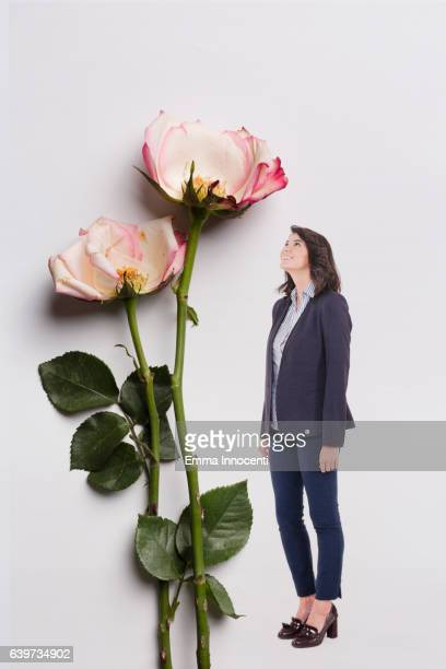 Young business woman standing next to a big rose