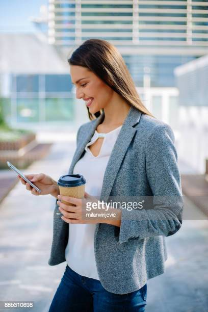 Young business woman using smartphone outdoors