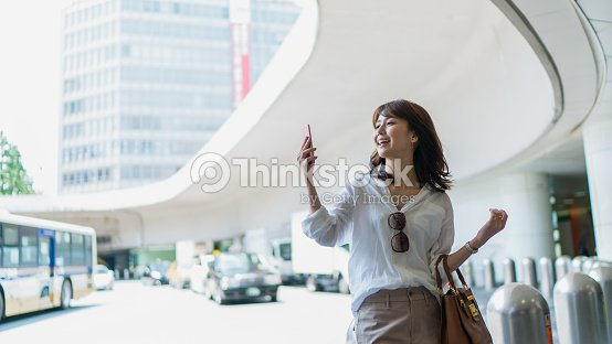 Young business woman watching mobile phone in a town : Foto de stock