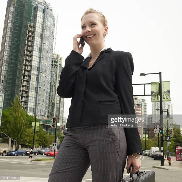 Young business woman with briefcase in the street talking on cell phone