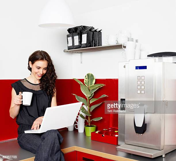 Young business woman with laptop in office kitchen
