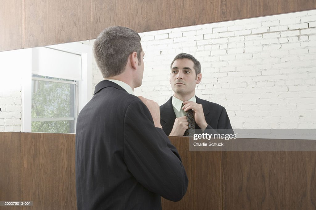 Young businessman adjusting tie in mirror : Stock Photo