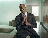 Young businessman adjusting tie, smiling, portrait