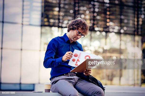 Young businessman analyzing financial data and charts for new business