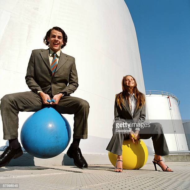 Young businessman and a young businesswoman sitting on space hoppers