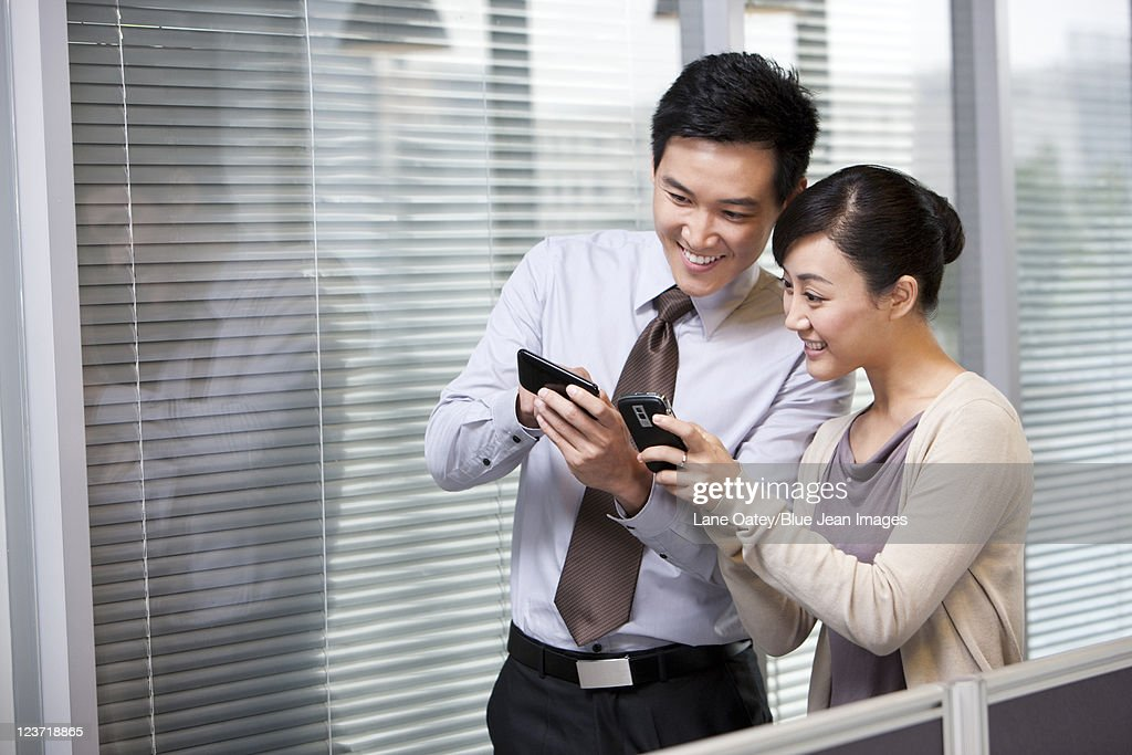 Young Businessman and Businesswoman Comparing Pictures : Stock Photo