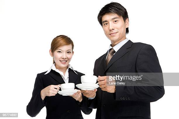 Young businessman and businesswoman having coffee together