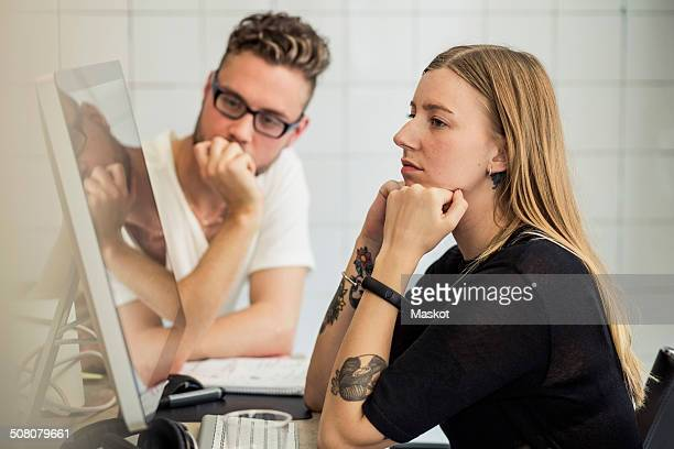 Young businessman and businesswoman looking at computer monitor in creative office