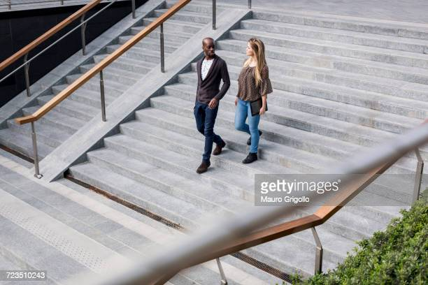 Young businessman and woman moving down city stairway talking