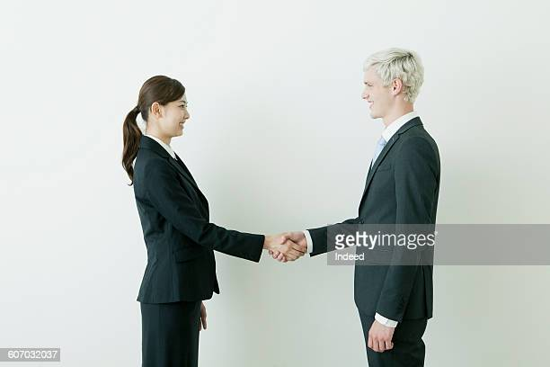 Young businessman and woman shaking hands