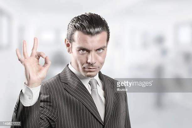 Young businessman approving with OK hand sign