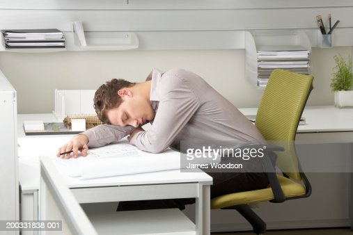 Young businessman asleep on desk
