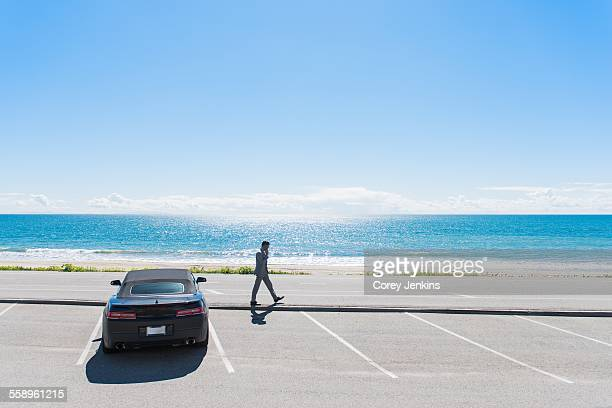 Young businessman at coastal parking lot walking whilst talking on smartphone