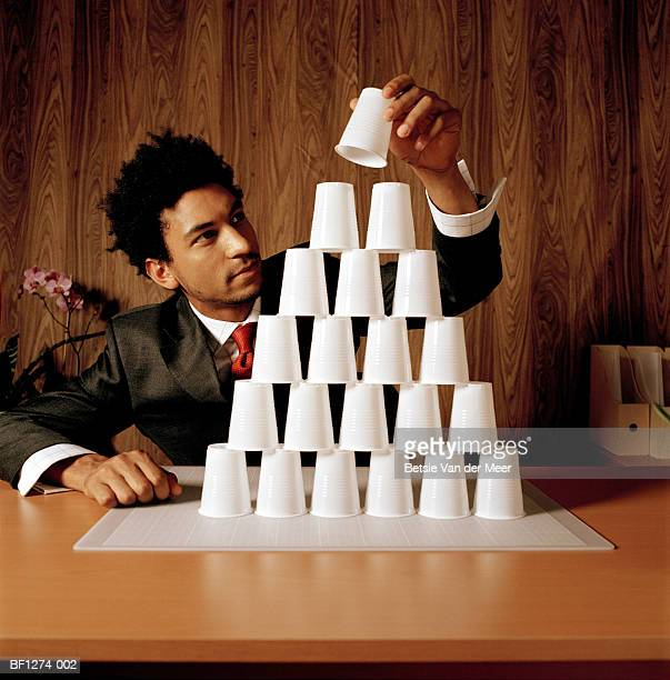 Young businessman at desk placing paper cup on top of stack, close-up