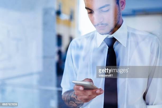 Young businessman behind glass pane looking at cell phone