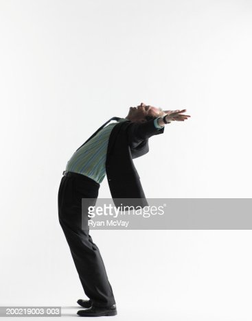 Young businessman bending backwards, arms outstretched, side view : Stock Photo