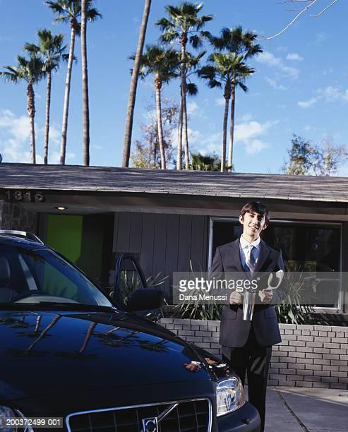 Young businessman beside new car, portrait