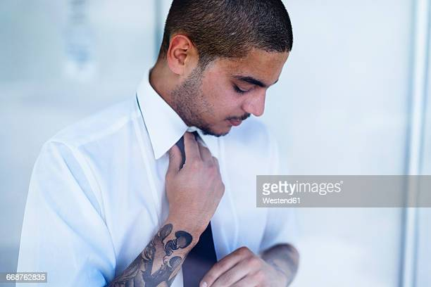 Young businessman binding tie