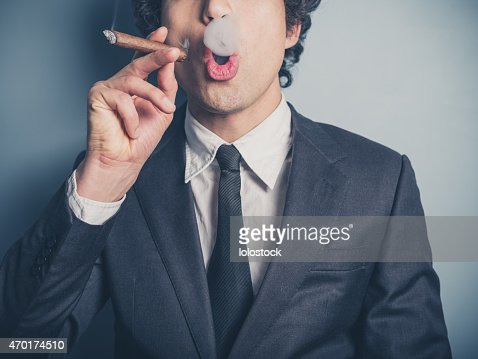 Young businessman blowing smoke rings : Stock Photo