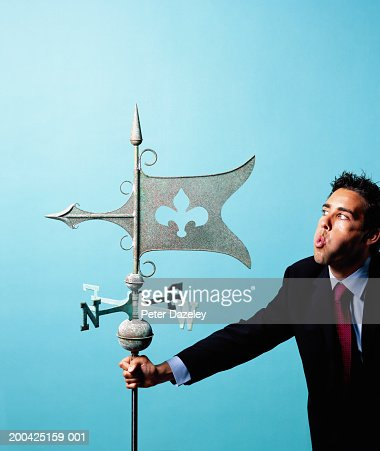 Young businessman blowing wind vane : Stock Photo