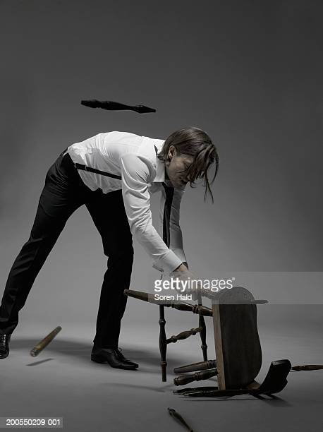 Young businessman breaking chair on floor