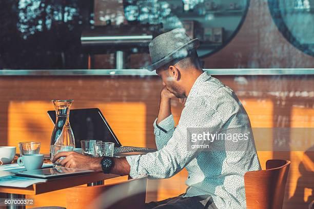 Giovane uomo d'affari occupato in Café, mattina, al lavoro