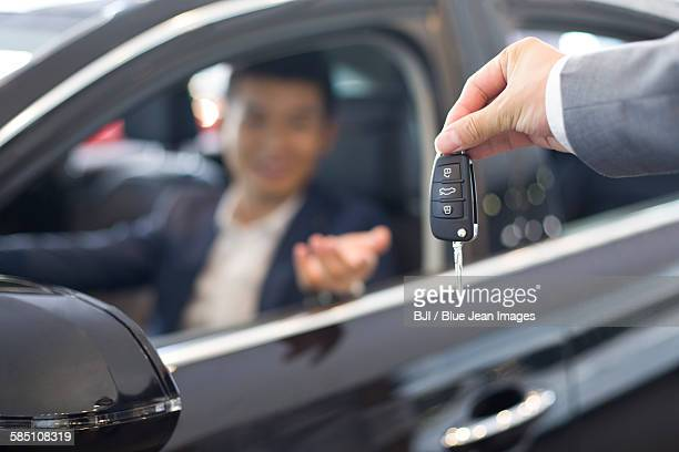 Young businessman buying car in showroom