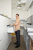 Young businessman by filing cabinet in office, portrait