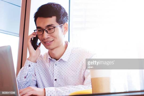 Giovane uomo d'affari Chiamata con il telefono cellulare e computer portatile