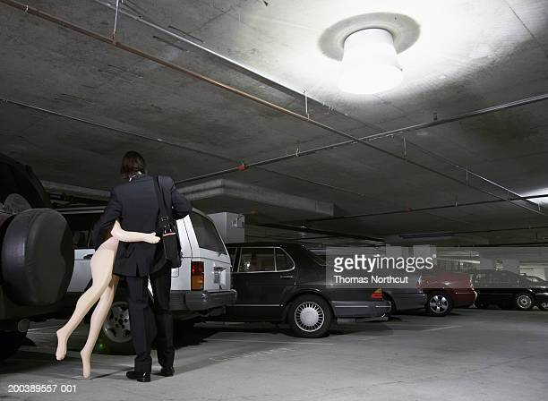 Young businessman carrying blow-up doll in parking garage, rear view
