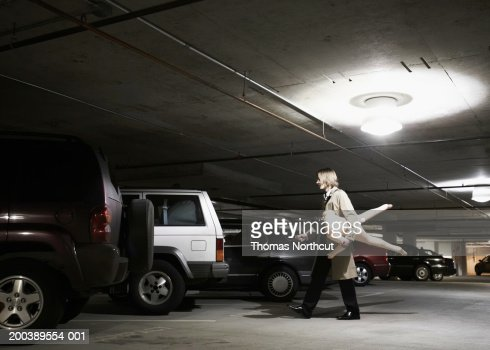 young businessman carrying blowup doll in parking garage side view stock foto getty images. Black Bedroom Furniture Sets. Home Design Ideas
